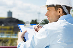后面观点的有剪贴板的男性建筑师在建造场所 免版税库存图片