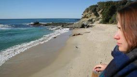 后面观点的有得到离在海洋海滩的篱芭较近的背包和围巾的年轻女人 股票视频
