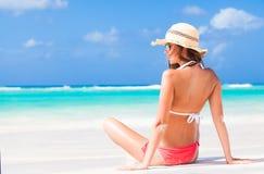 后面观点的有条纹的泳装和草帽的长发女孩在热带加勒比海滩 免版税图库摄影