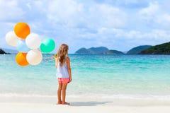 后面观点的有气球的小女孩在海滩 免版税图库摄影