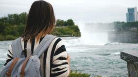 后面观点的有注视着正确,观看的瀑布尼亚加拉大瀑布慢动作的背包的愉快的地方白种人妇女 股票录像