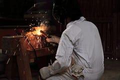 后面观点的有火炬和防毒面具焊接钢的专业焊工人与火花在工厂 行业概念 免版税库存照片