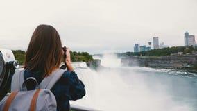 后面观点的有背包和使尼亚加拉大瀑布瀑布慢动作惊奇照相机照相的愉快的旅客妇女  影视素材