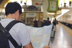 后面观点的有背包探索的地图的年轻亚裔游人在火车站 图库摄影