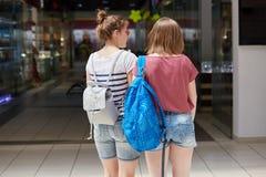 后面观点的有背包漫步的两位年轻女性在商城,做购买,穿牛仔布短裤和偶然T恤杉,尝试 免版税库存图片