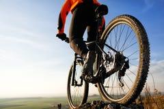 后面观点的有自行车的一个人反对天空 免版税库存图片
