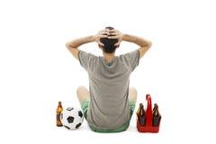 后面观点的有足球的一个年轻人和盒啤酒观看的橄榄球赛,看起来失望 查出的背面图白色 免版税库存图片