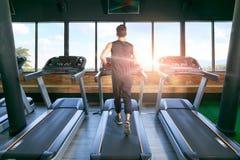 后面观点的有跑的年轻人运动员在健身房的踏车 库存图片