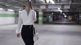 后面观点的有马尾、白色衬衫和黑裙子的逗人喜爱的女性在车库 股票视频