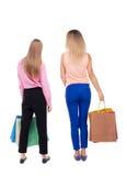 后面观点的有购物袋的两名妇女 库存照片