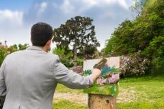 后面观点的有他的sketchb的一位英俊的中年男性艺术家 免版税库存照片