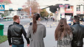 后面观点的朋友走在街道 英俊的人和两个俏丽女孩聊天忙个不停 Steadicam射击,缓慢的mo 股票录像