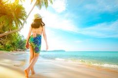 后面观点的桃红色泳装的愉快的年轻亚裔妇女和草帽放松并且享受假日在热带天堂海滩 女孩 免版税库存照片