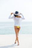 后面观点的比基尼泳装和海滩帽子的一名妇女 库存图片