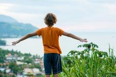 后面观点的热带海滩的一个小男孩 库存图片