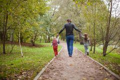 后面观点的父亲和他的两个小女儿 库存照片