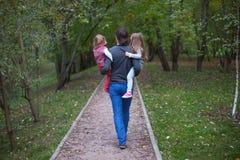 后面观点的父亲和他的两个小女儿 免版税库存图片