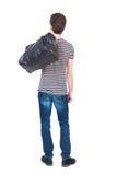 后面观点的牛仔裤的人有在他的肩膀的一个袋子的 图库摄影