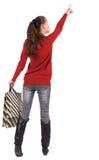 后面观点的牛仔裤的妇女有购物袋指向的。 免版税库存图片