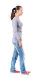 后面观点的牛仔裤的走的妇女 免版税图库摄影