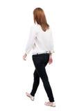 后面观点的牛仔裤的走的妇女 m的美丽的白肤金发的女孩 库存图片