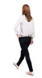 后面观点的牛仔裤的走的妇女 m的美丽的白肤金发的女孩 免版税图库摄影