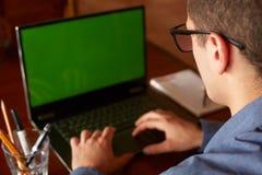 后面观点的玻璃工作的自由职业者人与膝上型计算机 绿色屏幕 做在个人计算机的白种人商人项目 免版税库存图片
