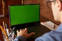 后面观点的玻璃工作的自由职业者人与膝上型计算机 绿色屏幕 做在个人计算机的白种人商人项目 图库摄影