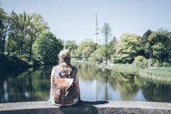 后面观点的白肤金发的妇女坐墙壁由池塘在公园在晴天 库存图片