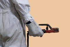 后面观点的白色一致的举行的电弧焊接火炬的专业焊工工作者在他的在背景的手上 免版税库存图片