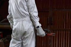 后面观点的白色一致的举行的电弧焊接火炬的专业焊工工作者在他的手上在有拷贝空间bac的工厂 库存图片