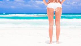 后面观点的白色比基尼泳装的少妇在海滩 库存图片