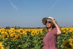 后面观点的看向日葵的帽子的妇女 图库摄影