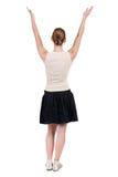 后面观点的看墙壁和举行的牛仔裤的美丽的妇女 免版税库存图片