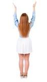 后面观点的看墙壁和举行的礼服的美丽的妇女 图库摄影