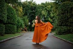 后面观点的站立在路的长的橙色礼服的美丽的微笑的妇女 图库摄影
