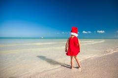 后面观点的红色帽子的圣诞老人小逗人喜爱的女孩 库存照片