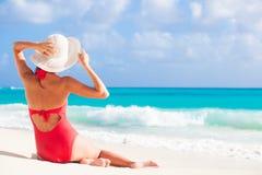 后面观点的红色游泳衣和草帽的妇女 免版税库存图片