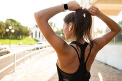 后面观点的耳机的一个年轻健身女孩 免版税库存图片