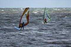 后面观点的行动的两个风帆冲浪者在多暴风雨的天气 免版税库存照片