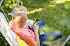 后面观点的资深老人在夏日递在电话的卷动有色度绿色屏幕的 免版税图库摄影