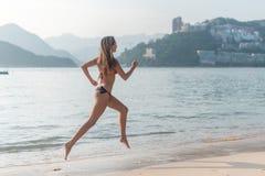 后面观点的赤足跑在海滨佩带的比基尼泳装的适合亭亭玉立的女孩 做心脏锻炼海滩的少妇点燃了  图库摄影