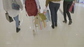 后面观点的走和运载在购物中心的一个小组年轻时髦的女人购物袋- 股票录像