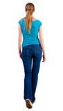 后面观点的走的妇女 牛仔裤和衬衣。 免版税库存照片