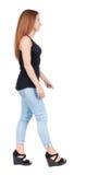 后面观点的走的妇女 行动的美丽的红头发人女孩 图库摄影
