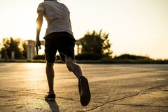 后面观点的跑在日落的都市城市的偶然剪影的年轻人运动员 库存照片