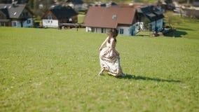 后面观点的转动在周围在草甸的长的土气礼服的女孩在山的背景 股票视频