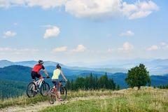 后面观点的运动员循环越野的运动服和盔甲的夫妇骑自行车者骑自行车 库存图片