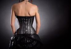 后面观点的银色皮革束腰的妇女 免版税库存照片