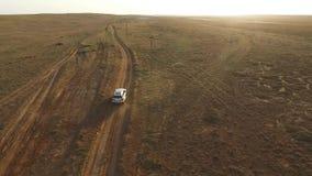 后面鸟瞰图:驾驶在日落前面的一个干草原的大银色SUV 股票视频